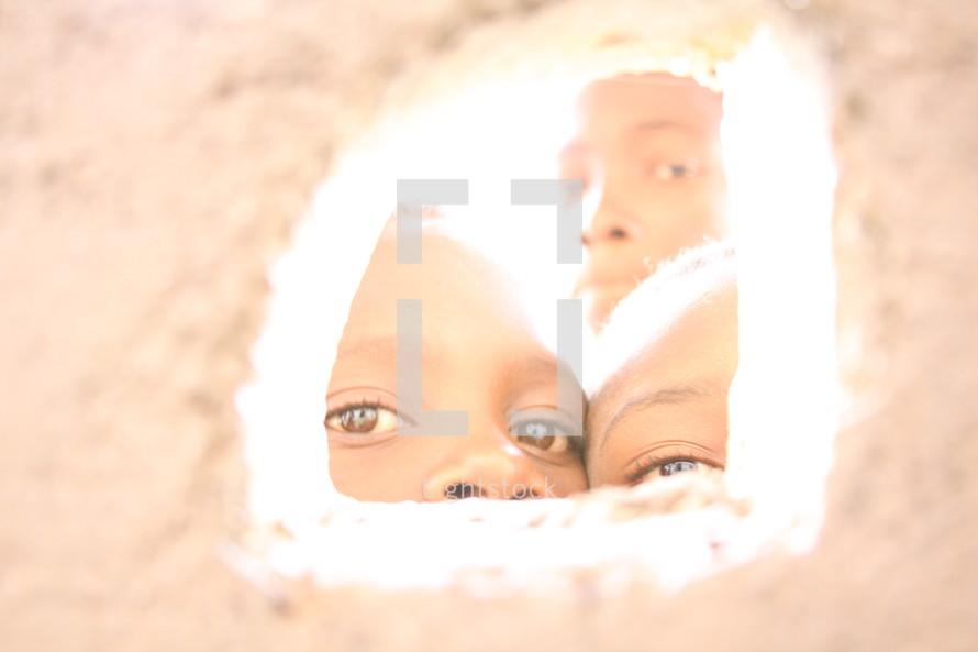 eyes of children peeking through a small window