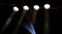 Concert stage with white spotlights and smoke
