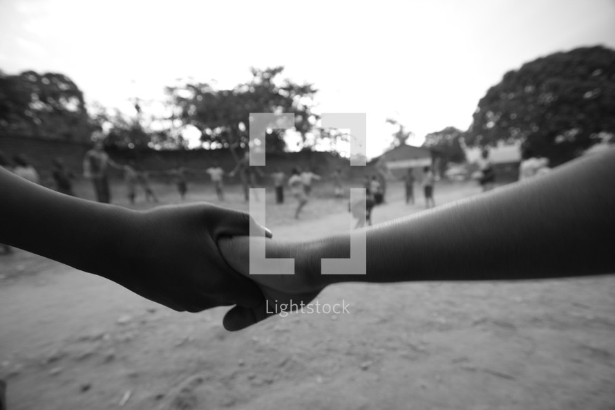 Black and white children holding hands  while playing a game.