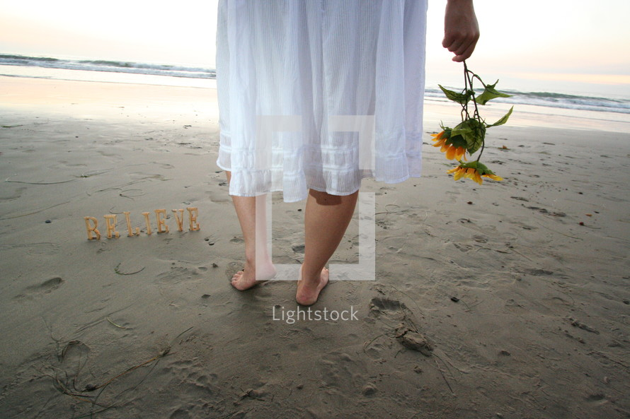 word BELIEVE on sand and woman in bare feet holding flowers