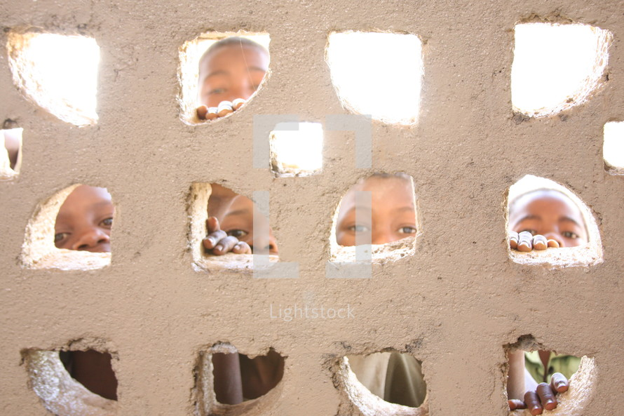 Children looking through small windows