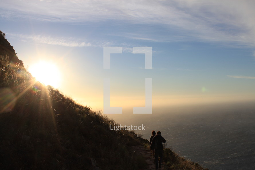 sun moving behind a hill as people walk along a path along a coastline