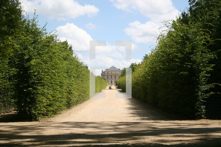 long dirt driveway leading to a chateau