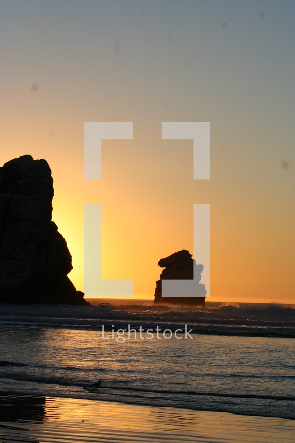 rock formations in the ocean at sunset