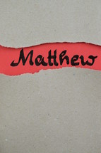 Matthew - torn open kraft paper over light red paper with the name of the Gospel of Matthew