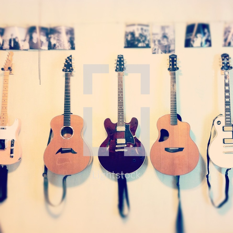row of guitars hanging on a wall