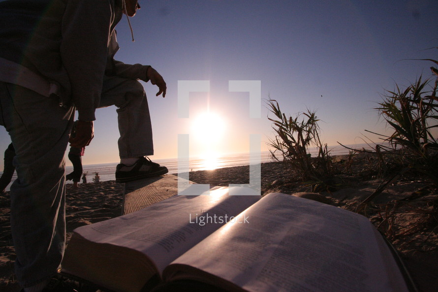 man crouched on a bench next to an open Bible