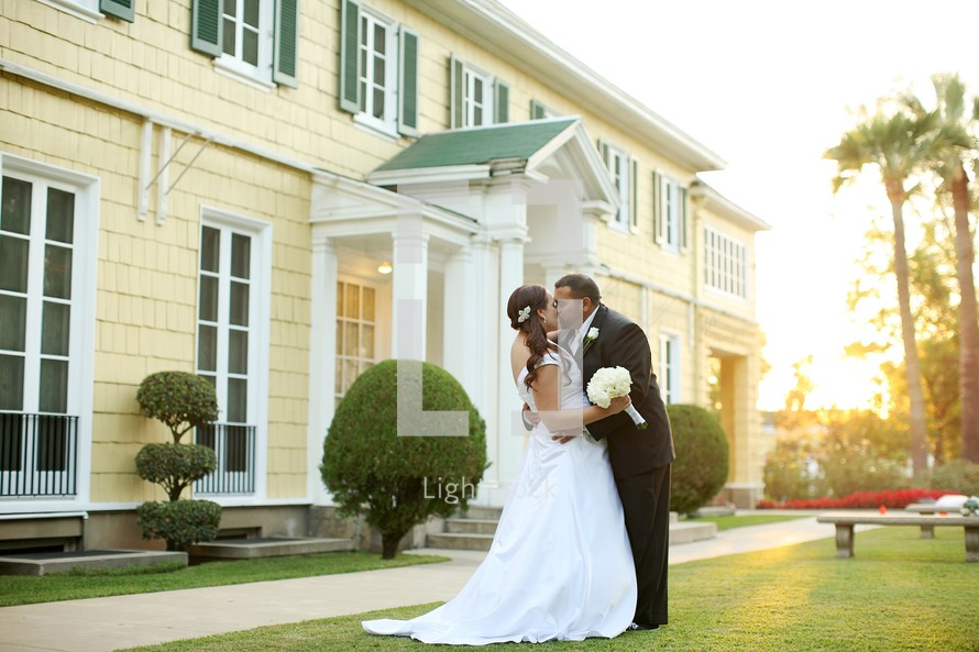 Bride and groom kissing outdoors