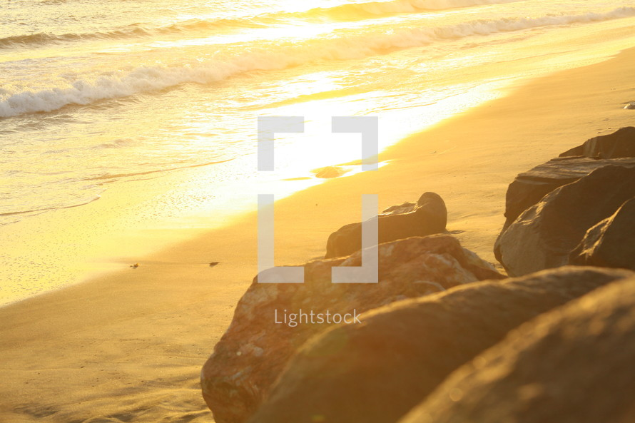 Rocks by the beach at sunset