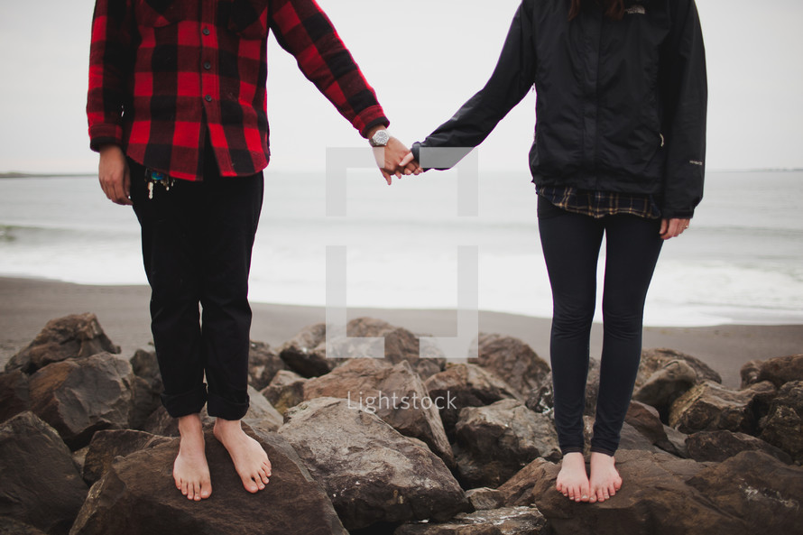 A couple standing on rocks holding hands
