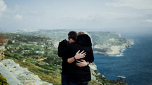 a couple hugging with an ocean view