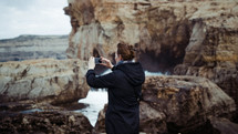 a woman taking a picture of waves crashing into rocks with her phone