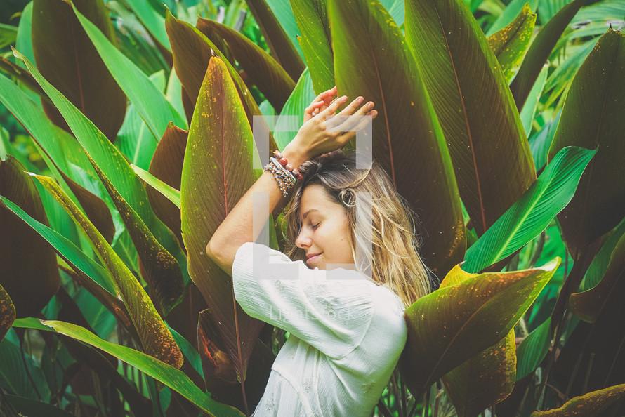 a woman standing amongst tropical plants