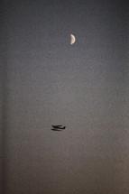 sea plane in flight under a crescent moon