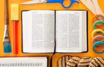 open Bible, open Hymnal, paint brushes, cookies, scissors, tape and popsicle sticks on orange background