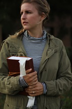 a young woman in a coat holding a Bible