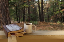Bible and coffee mug on a railing outdoors