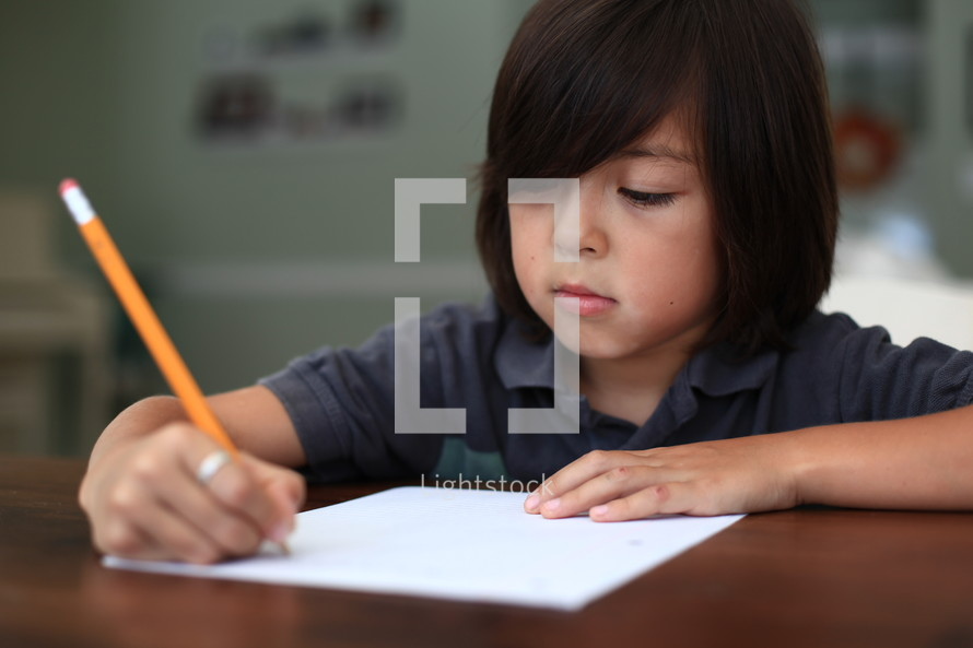 Boy writing on paper with pencil