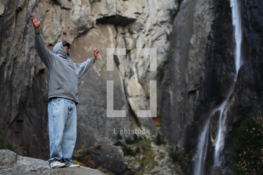 Man on mountain with raised hands
