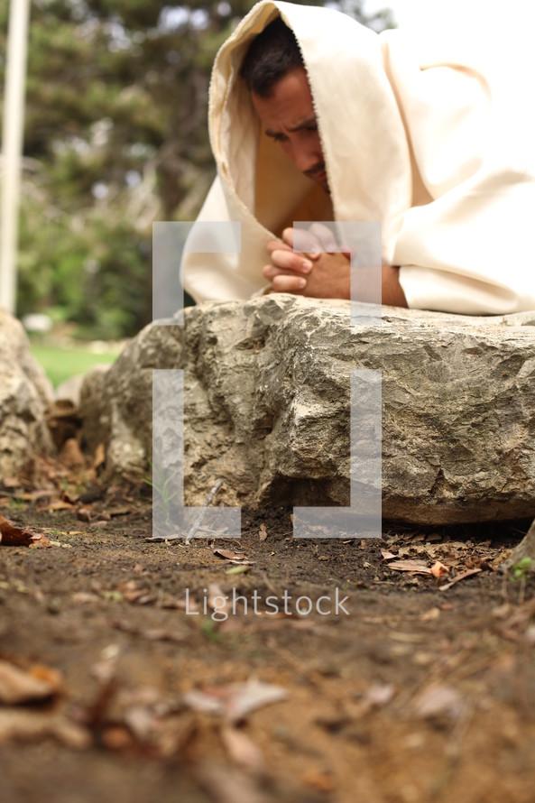 Jesus kneeling in prayer