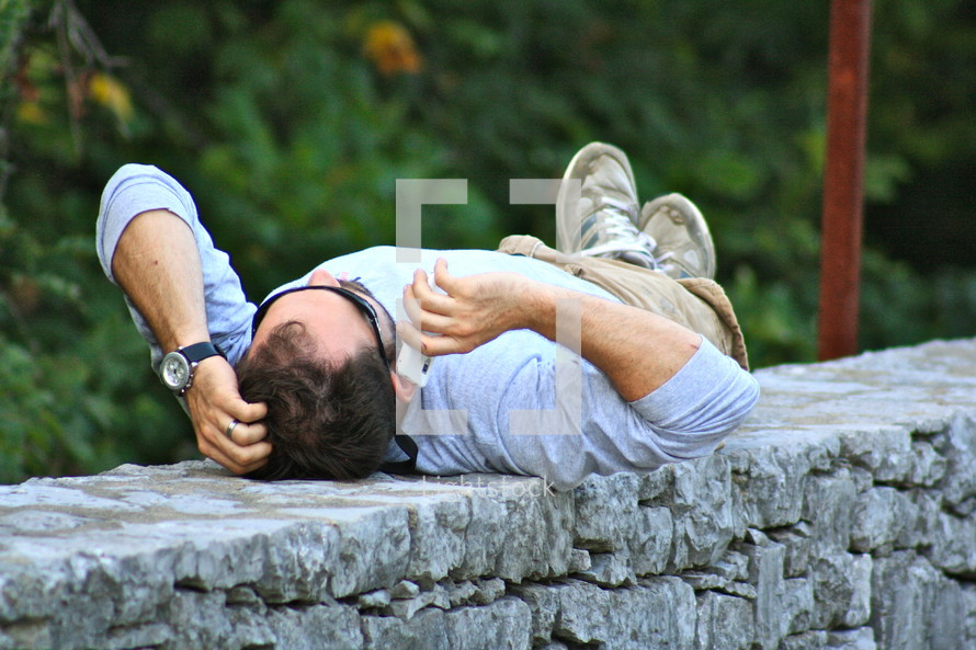Man lying on back, outdoors, on cell phone