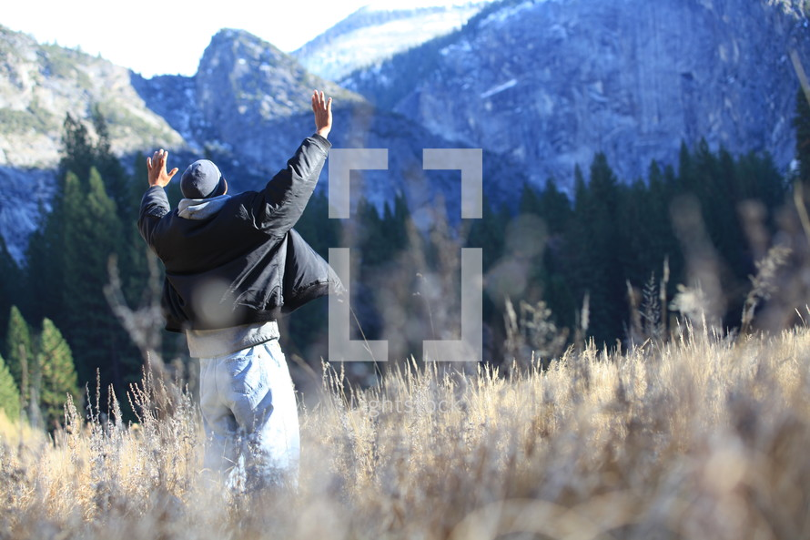 Man in open field with hands raised