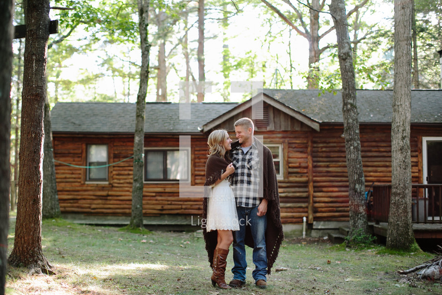 a couple wrapped in blankets in front of a log cabin