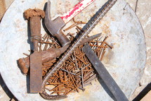 Rusty nails, crow bar and hammer on a mission project