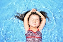 a toddler girl floating in a pool