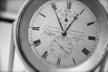 roman numerals clock or pocket watch showing five minutes before one o clock