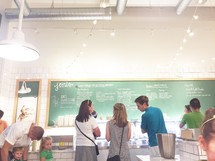 people in line ordering food from a menu at restaurant