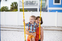 grandmother pushing her grandson on a swing
