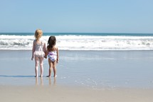 sisters in bathing suits holding hands on a beach