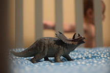 a dinosaur toy in a crib and infant