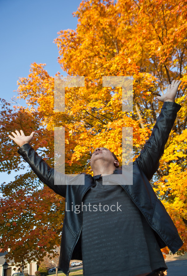 man with his hands raised in worship to God under fall leaves