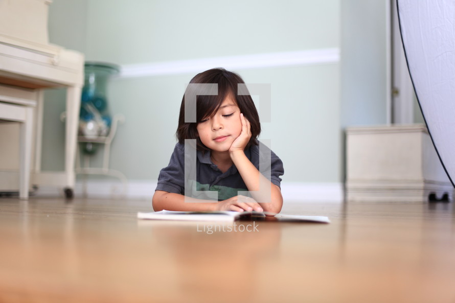 young boy lying on the floor reading