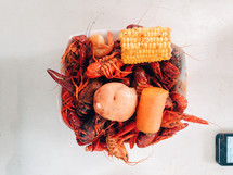 Crawfish boil in a bowl with a potato, carrot, and corn on the cob.