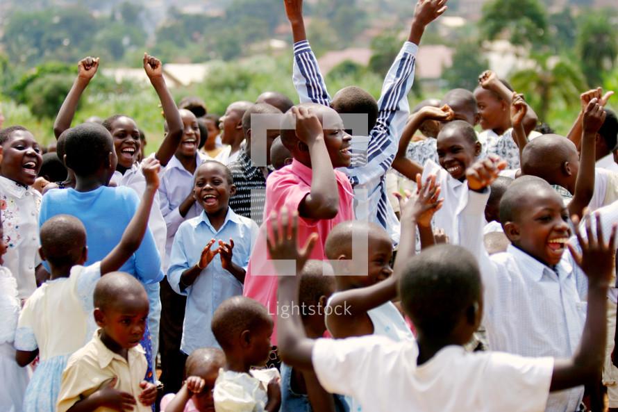 Group of African children youth  praising God joy dancing