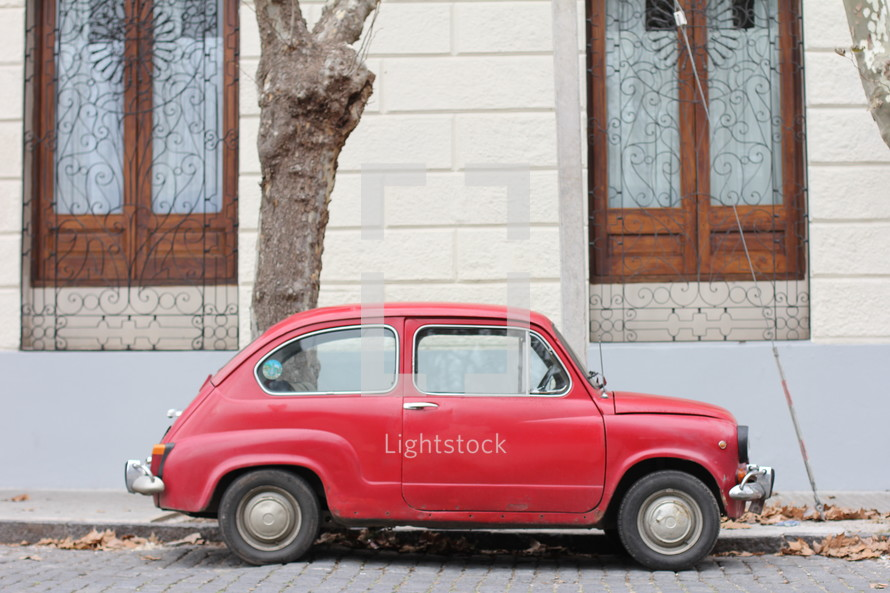 Small red car parked on a street