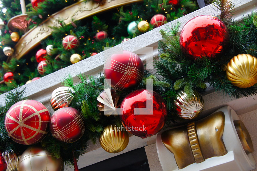 Red and gold ball Christmas ornaments and pine needles hangind from fireplace mantle.