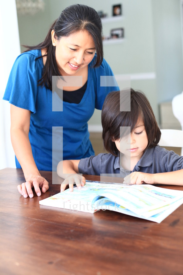 Mother helping son read book