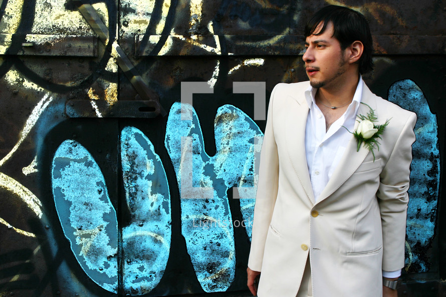 groom standing in front of a graffiti covered wall