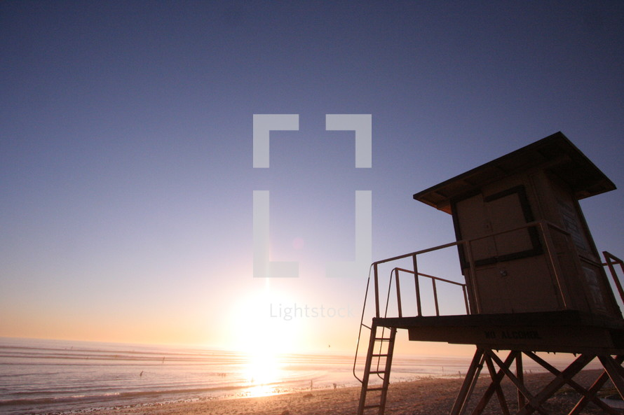 sunset on a beach near a lifeguard stand