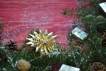 pine needles, ornaments, pine cones, and snow on a red background