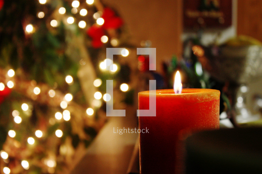 candle burning in front of a Christmas tree