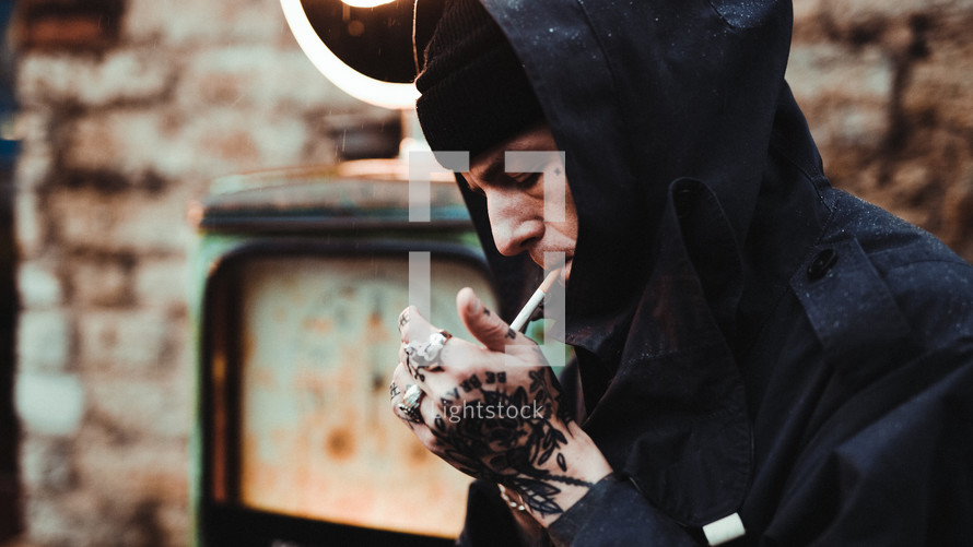 man with tattooed hands smoking a cigarette
