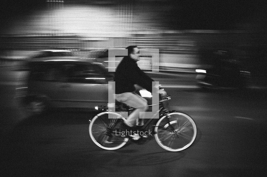 man riding his bicycle on a busy street