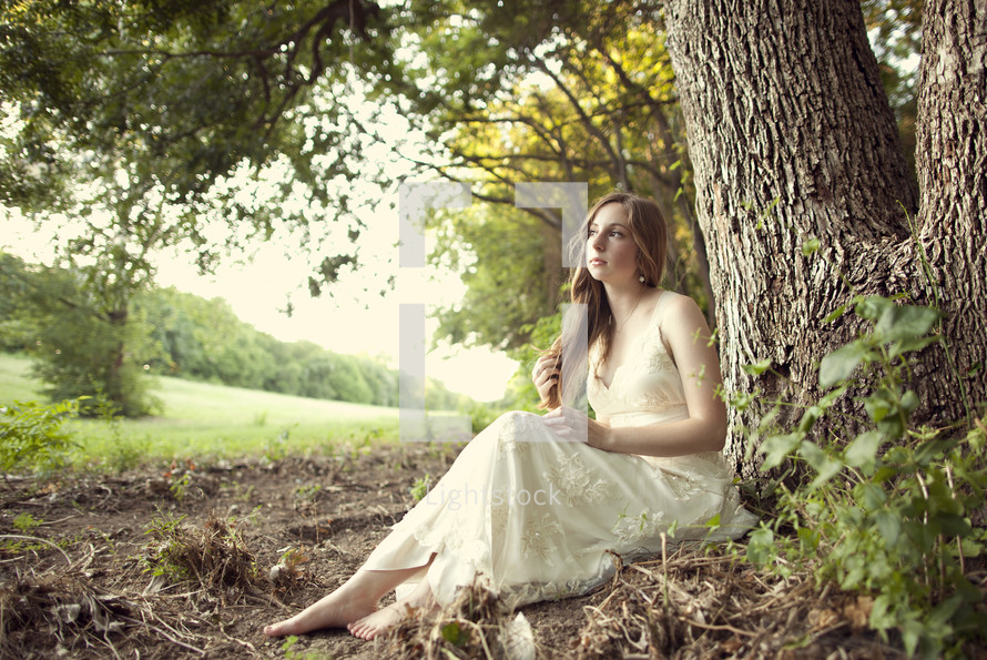 woman in a lace dress sitting under a tree