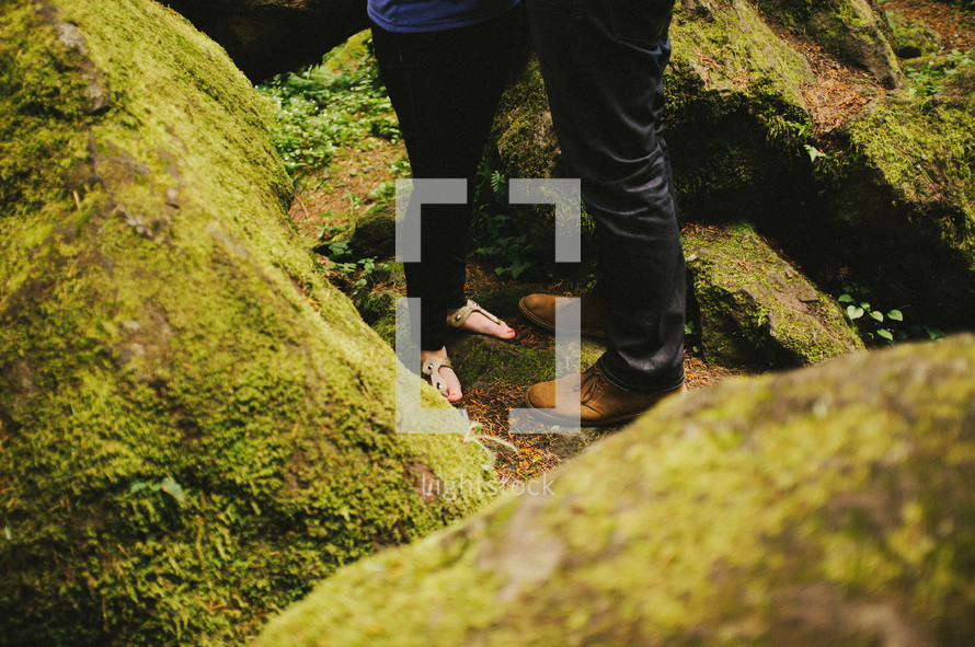 feet of a couple standing on moss covered rocks