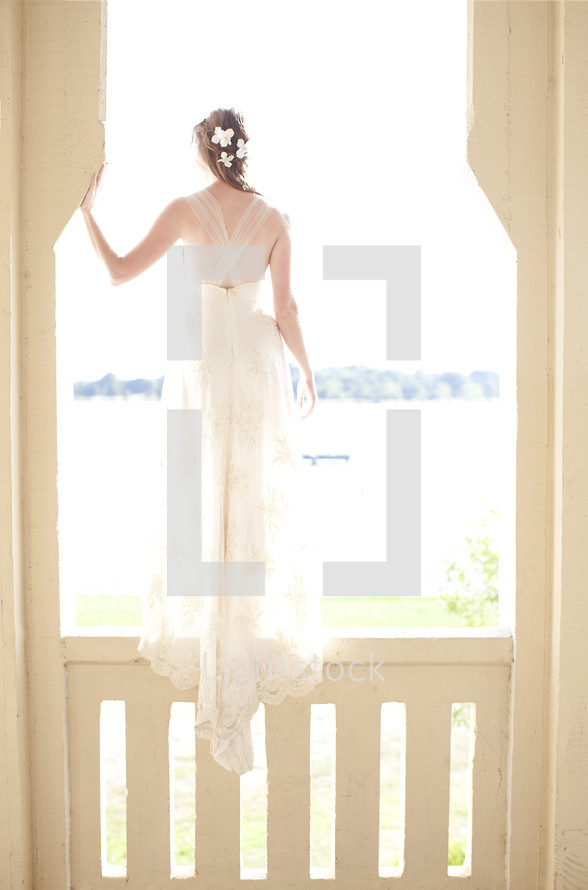 A woman in a white dress stands on a rail